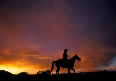 Photo: A cowboy is silhouetted against a colorful sky after a storm.
