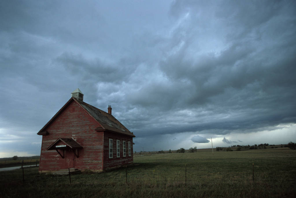 Photo: An old one-room school house amongst storm clouds.