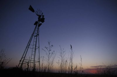 Photo: A lone windmill against a sunset sky.
