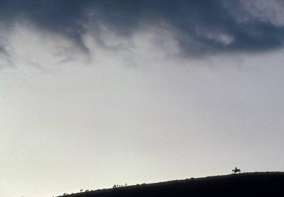 Photo: A man on a horse is silhouetted against a looming stormy sky.