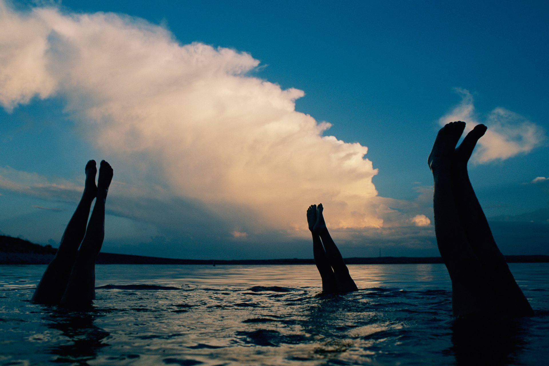 Photo: Three pairs of legs stick out of the water in Lake McConaughy, as a thunderstorm creeps forward in the distance.