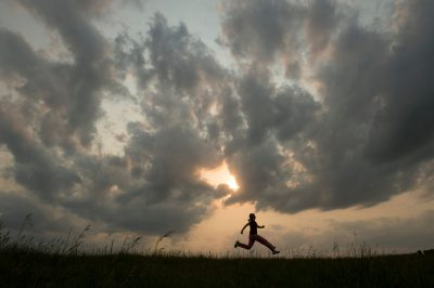 Photo: A young girl jumps accross a grassy field near Loma, Nebraska.