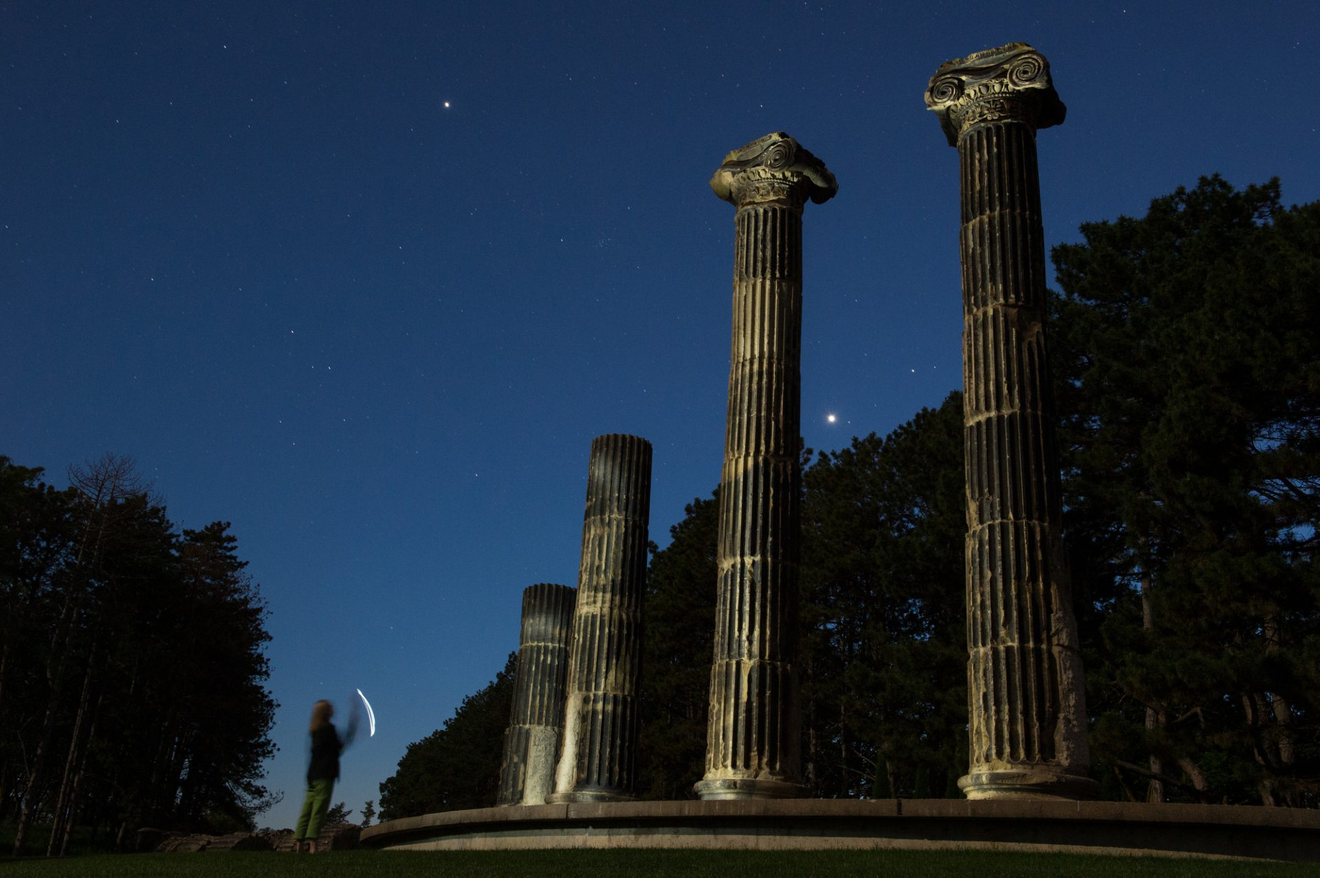 Photo: A woman shines a flashlight on historic columns at Pioneers Park in Lincoln, Nebraska.