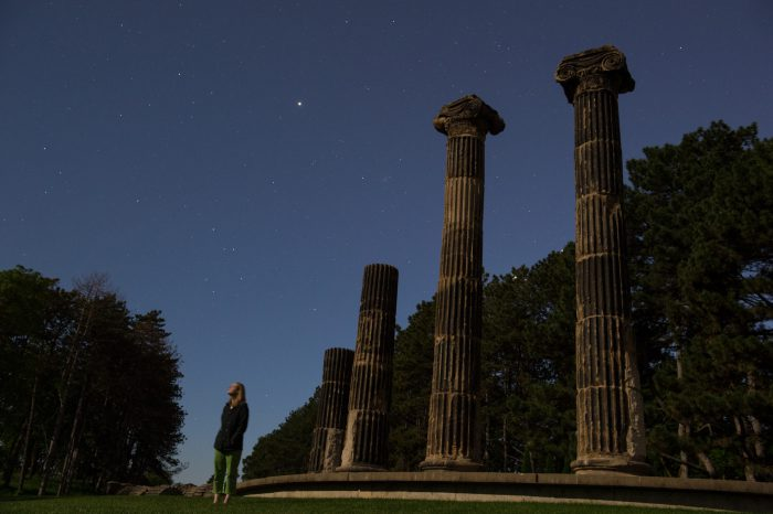 Photo: A woman looks at the stars near historic columns at Pioneers Park in Lincoln, Nebraska.