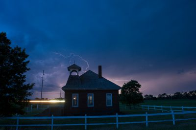 Photo: A one room school house with lightning in the background.