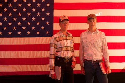 Photo: Two young cowboys stand in front of an American flag at Husker Harvest Days in Grand Island, Nebraska.