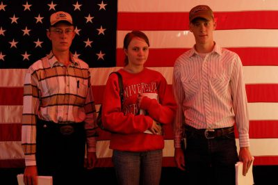 Photo: Three young adults stand in front of an American flag at Husker Harvest Days in Grand Island, Nebraska.