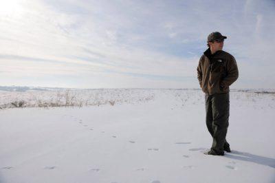 Photo: A man stands in a snowy pasture near Valparaiso, NE.