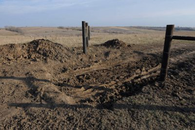 Photo: Wooden fence posts and depressions made in the ground mark the place of a future cattle guard in Valparaiso, NE.