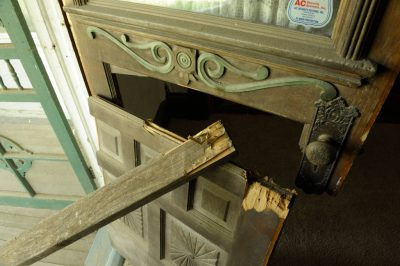 Photo: A broken front door stands open.