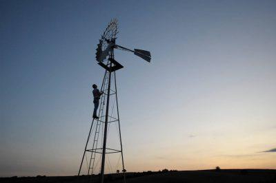 Photo: A man climbs a windmill tower.