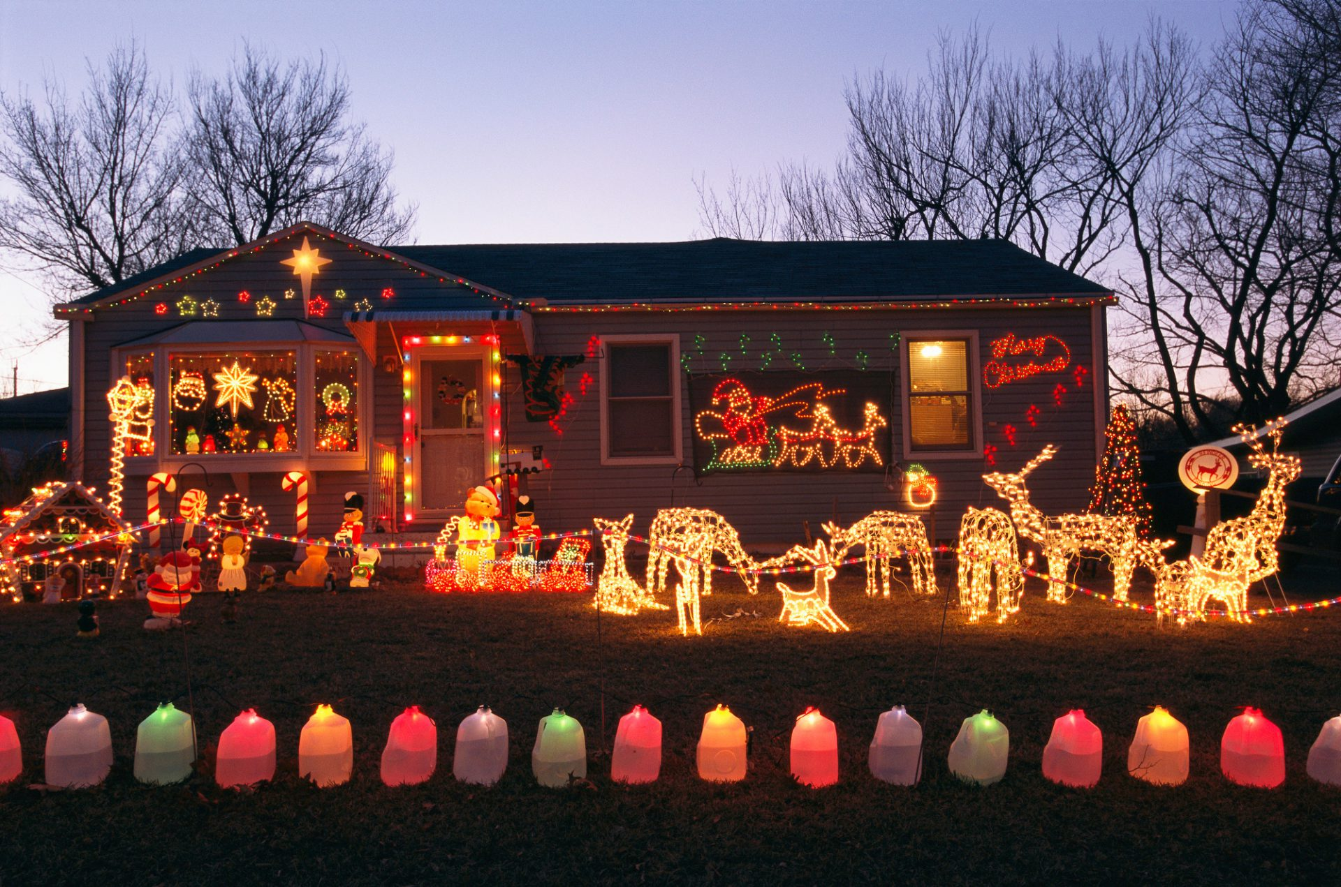 Photo: A house and front yard with brightly colored Christmas decorations.