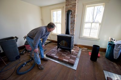 Photo: A man with newly-installed wood stove at the Dunbar farmhouse.