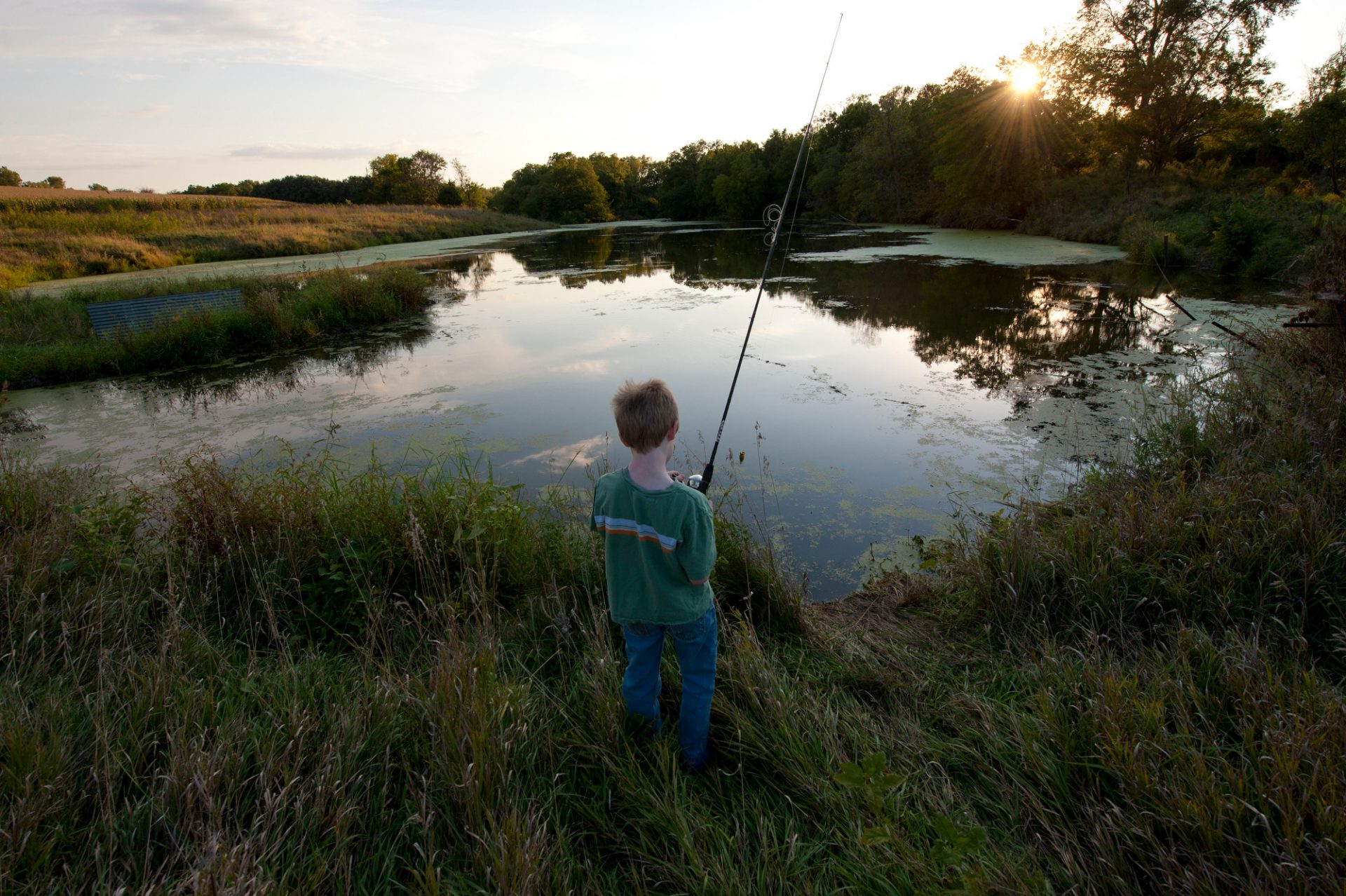 Photo: A young boy fishes in a pond near Ceresco, Nebraska.