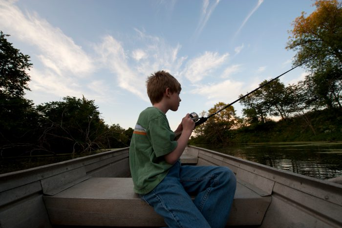 Photo: A young boy fishes from a boat near Ceresco, Nebraska.