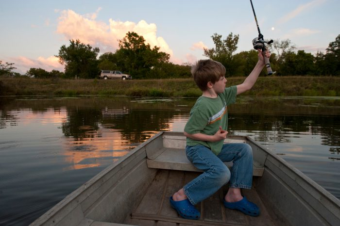 Photo: A young boy casts his fishing line from a boat near Ceresco, Nebraska.