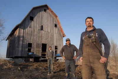 Photo: Three men relocate an old barn.