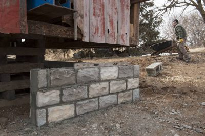 Photo: A mason works to instal a rough-faced block foundation for a barn.