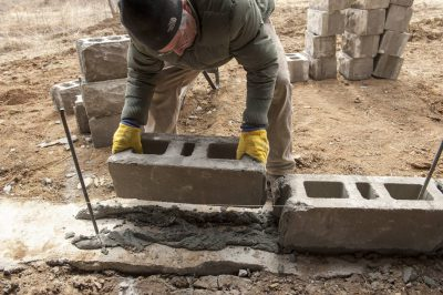 Photo: A mason works to instal a rough-faced block foundation.