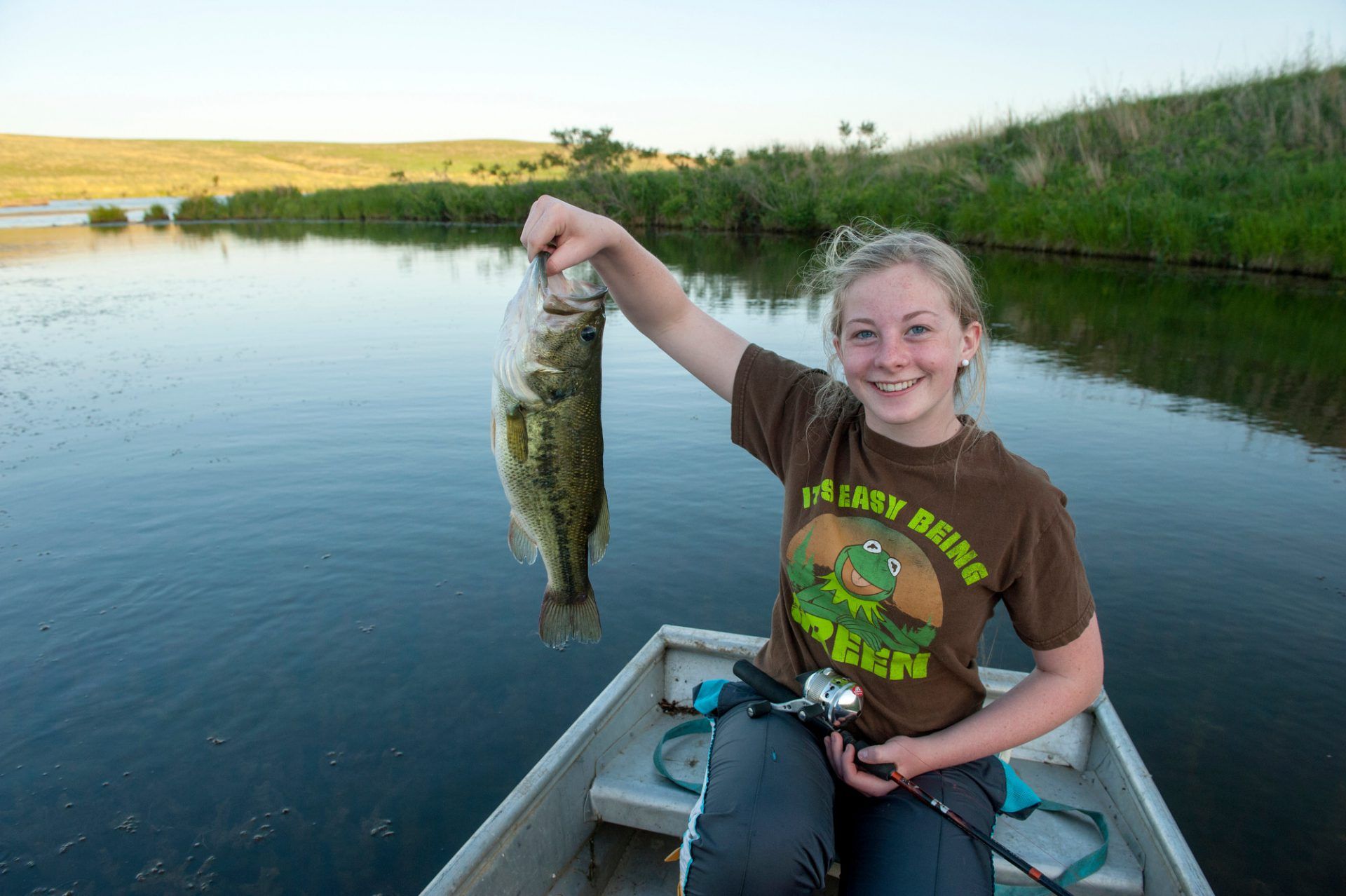 Photo: A teenage girl catches a fish out of a pond near Valparaiso, Nebraska.