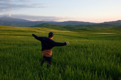 Photo: A young boy runs through a field of tall grass near Pienza.