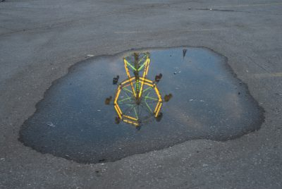 Photo: A Midway ride reflected in a puddle at the Nebraska State Fair.