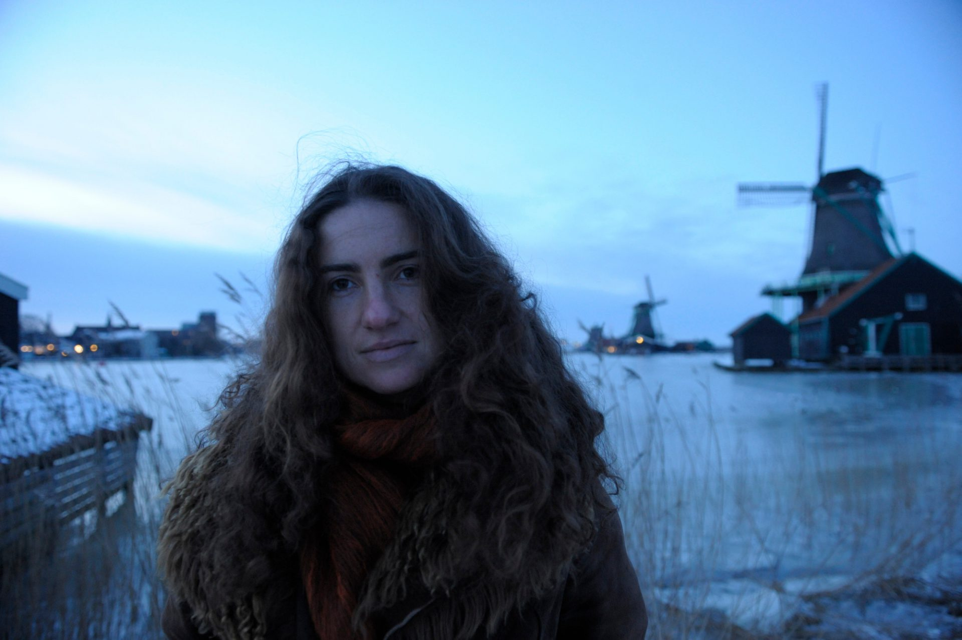 """Photo: A young woman stand in front of """"Zaanse Schans"""", a historic windmill area, in Amsterdam, The Netherlands."""