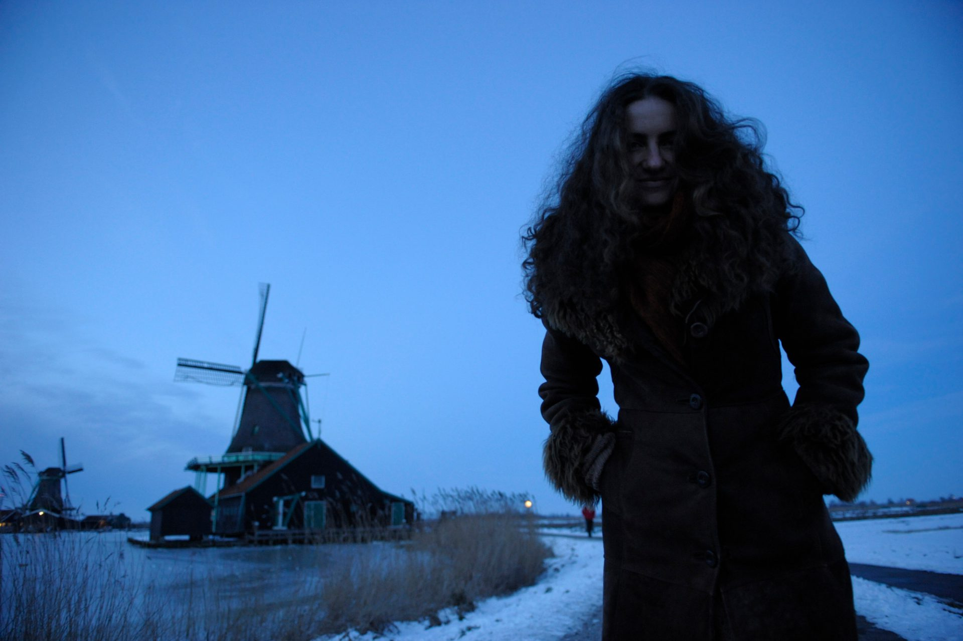 "Photo: A young woman stand in front of ""Zaanse Schans"", a historic windmill area, in Amsterdam, The Netherlands."