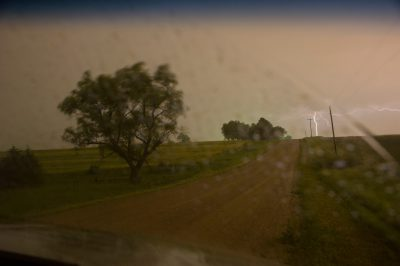 Photo: A landscape with a gravel road during a thunderstorm.