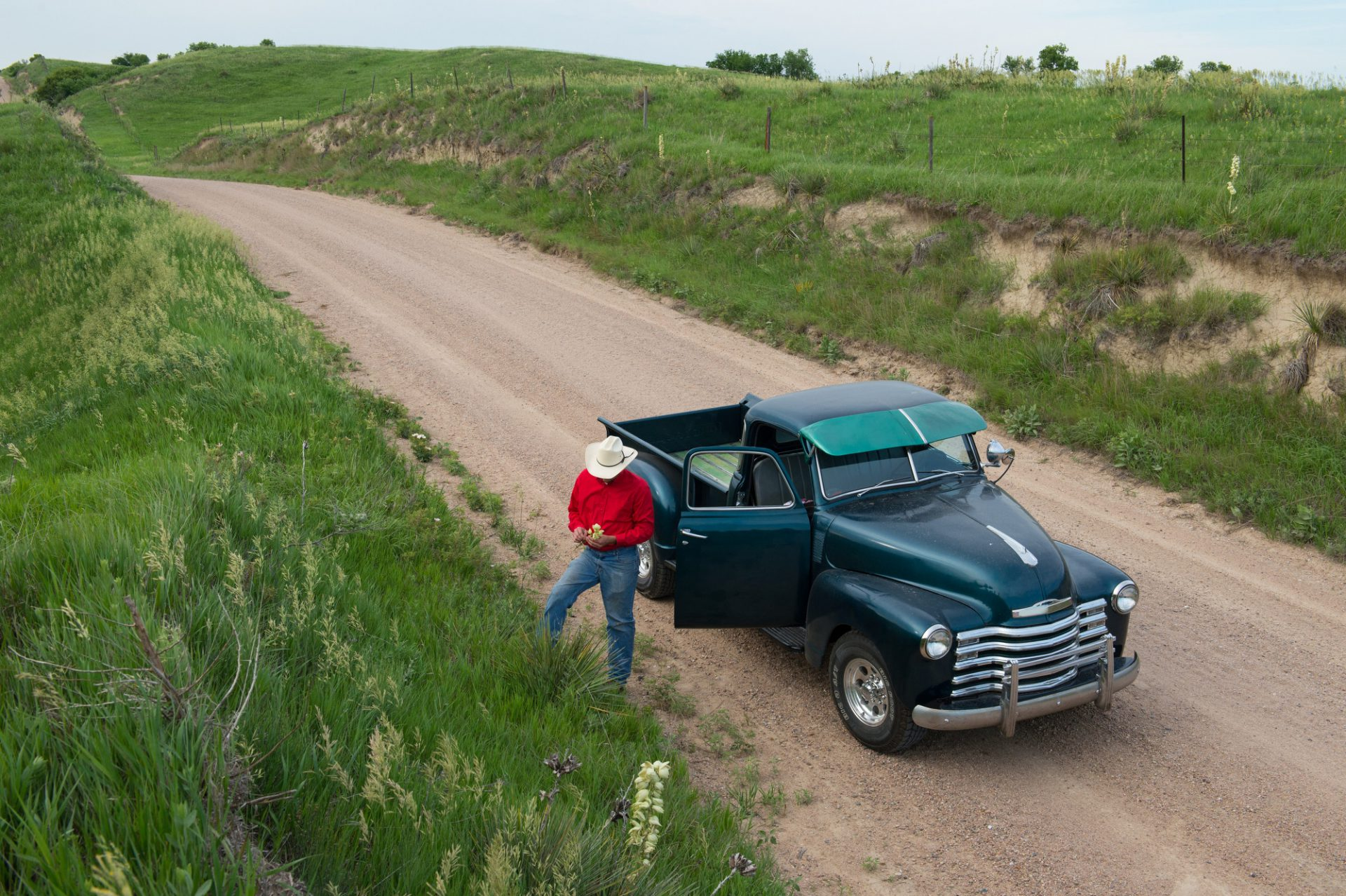Photo: A young man in a cowboy hat picks a flower near his truck on a gravel road.