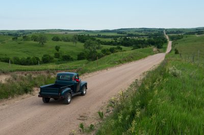 Photo: A father and son drive their truck down a gravel road.