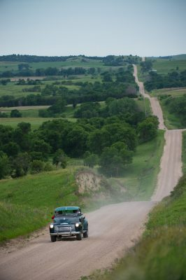 Photo: A father and son drive their truck up a gravel road.