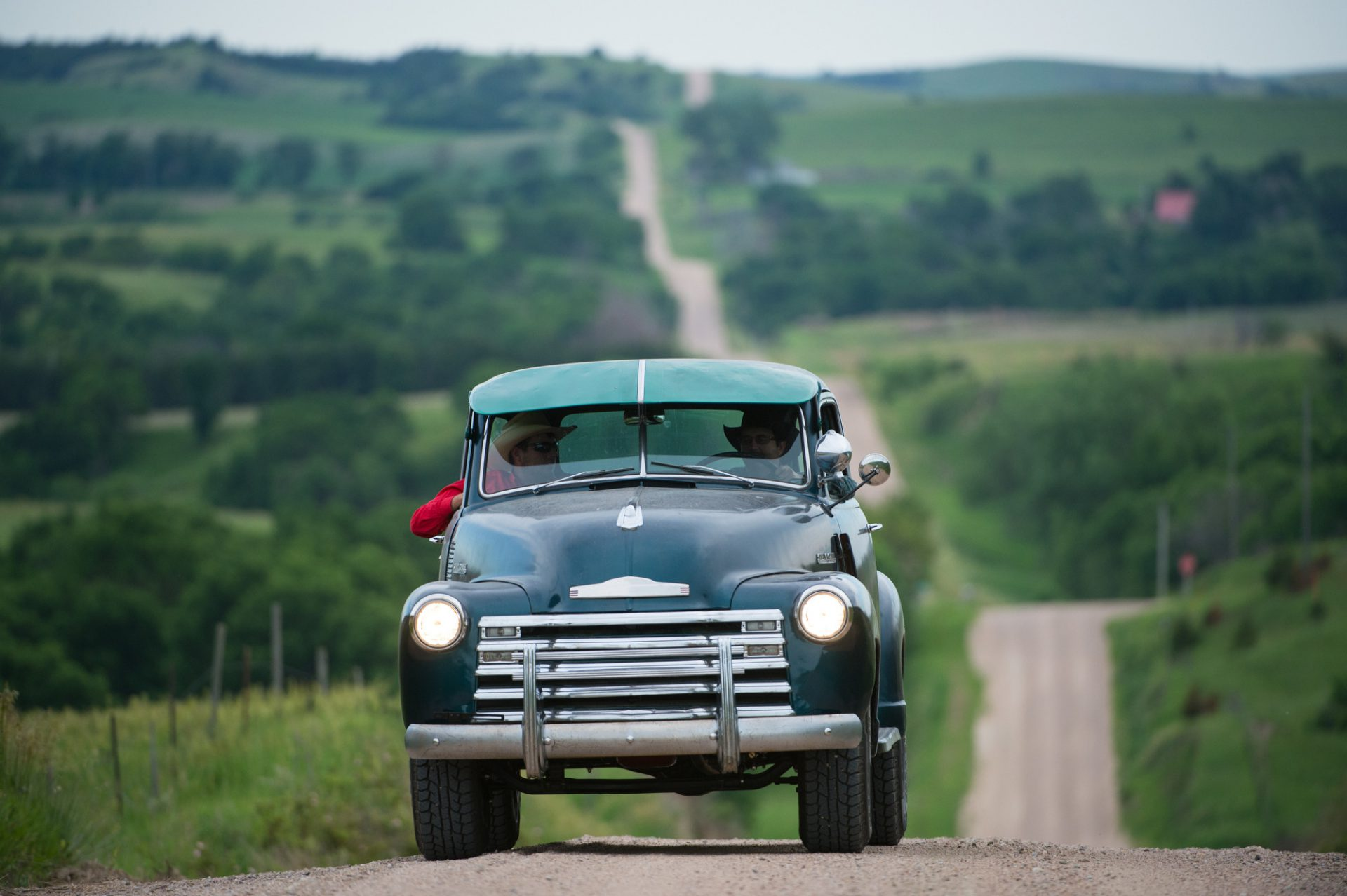 Photo: A father and son drive their truck on a gravel road.