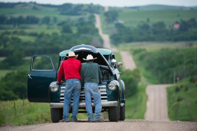 Photo: A father and son look under the hood their truck on a gravel road.