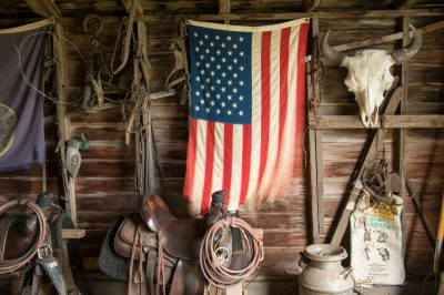 Photo: A still life with an American flag and saddle in a barn.