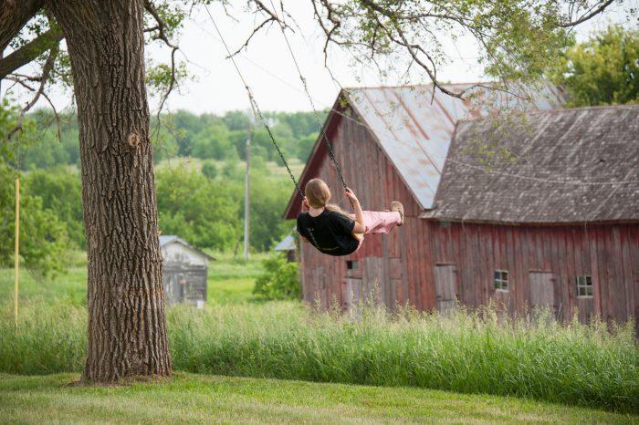 Photo: A teenage girl swings at her farm near Dunbar, Nebraska.