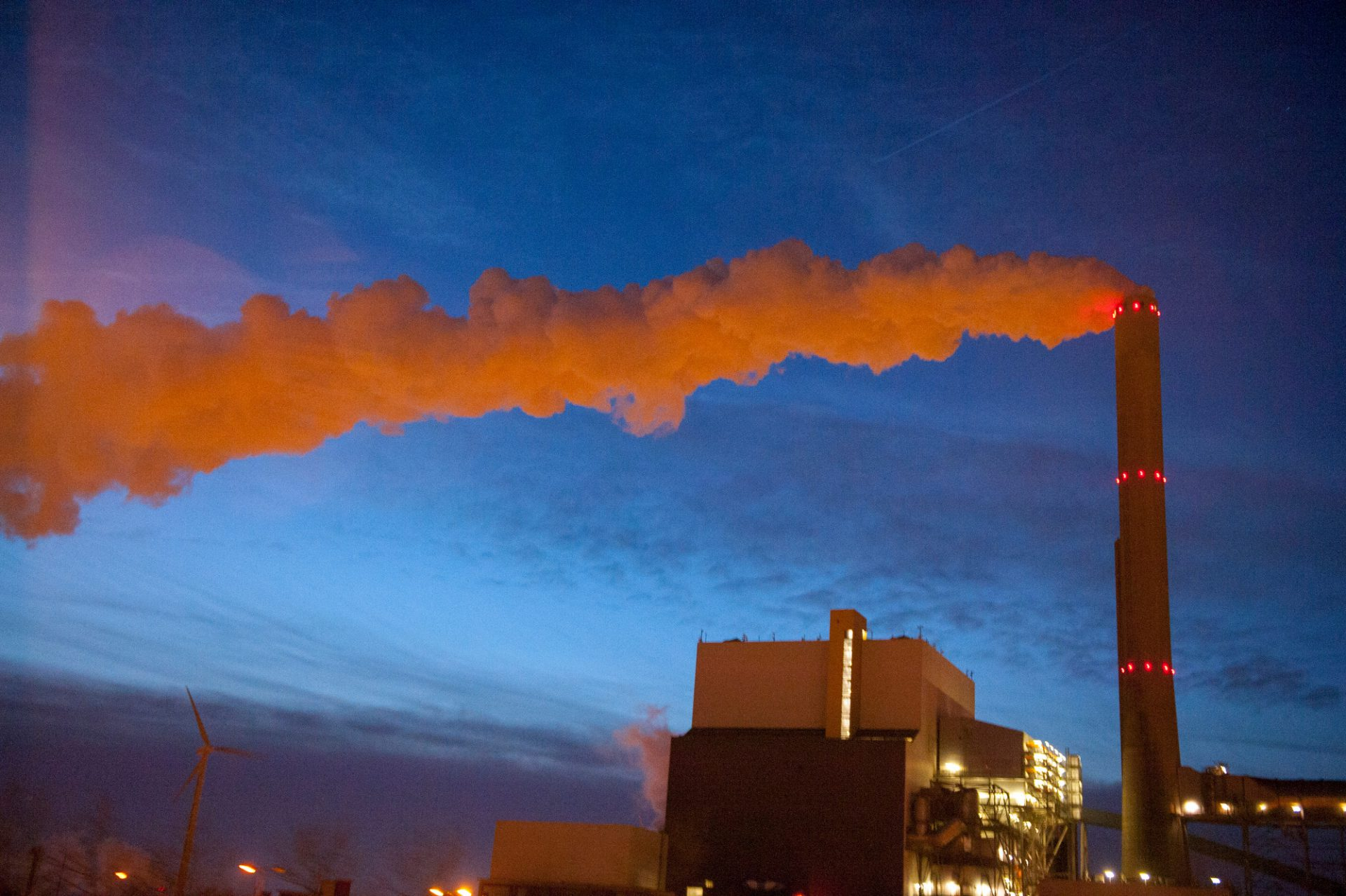 Photo: Steam from an industrial plant glows at night.