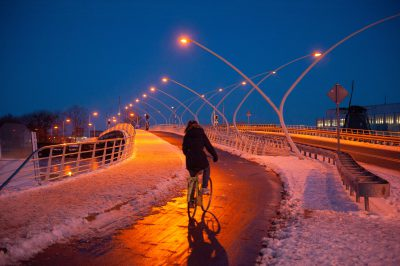 Photo: A lone cyclist bikes over a bridge at night.