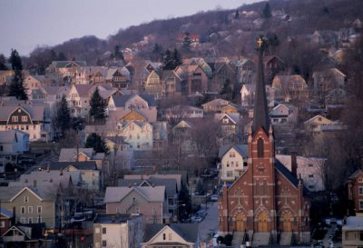 Photo: View of a church nestled among houses in Waterbury, CT.