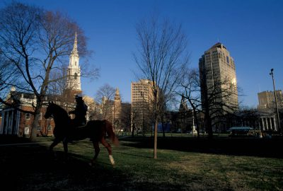 Photo: A mounted police officer rides past a church off New Haven Green in New Haven, CT.