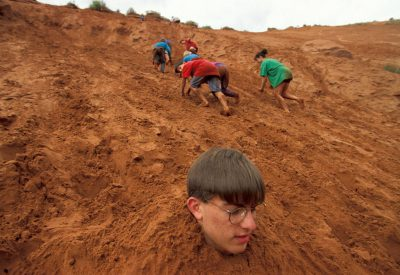 Photo: Children play in a sand dune north of Moab, Utah.