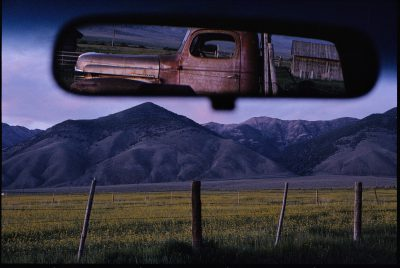 Photo: An old truck and barn are reflected in a rear-view mirror.