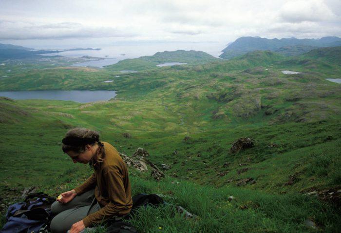 Photo: A woman snacks on an orange atop Mt. Reed on Adak Island in Alaska.