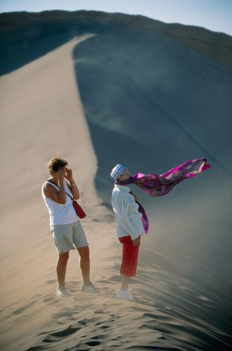 Photo: Two tourist are transfixed by the otherworldly terrain of the Valley of the Moon in Chile's Atacama desert.