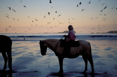 Photo: A young girl rides her horse at dusk on the beach near Tofino, Vancouver Island, British Columbia.
