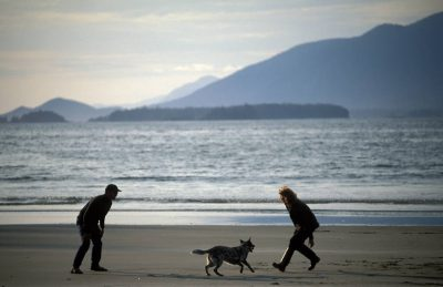 Photo: A couple play with their dog on the beach of Clayoquot Sound near Tofino, British Columbia.