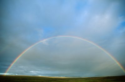 Photo: A rainbow spreads across the sky and over the tundra at Toolik Lake on the North Slope of Alaska.