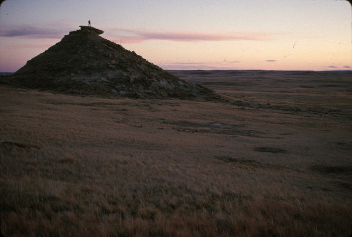 Photo: A person stands atop a rock formation in the scenic Charles M. Russell National Wildlife Refuge, Montana, along the Lewis and Clark route.