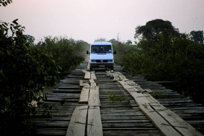 Photo: A van crosses a rickety wooden bridge spans a marshy area on the Transpantaniera highway in Brazil's Pantanal region.