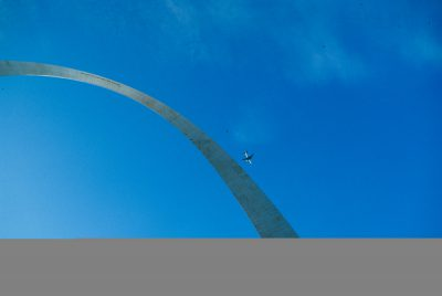 Photo: Abstract view of the St. Louis Arch, with a plane flying by.